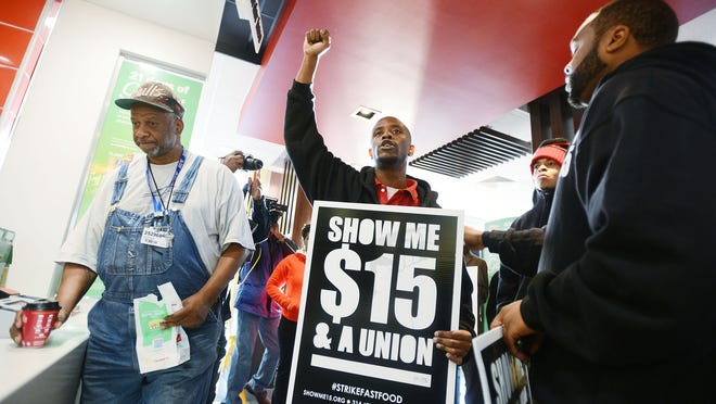 "In this Thursday, Dec. 4, 2014, file photo, a customer, left, stands at the counter as a group of protesters demonstrate inside the McDonald's restaurant on Northside Drive at Hanging Moss Road in Jackson, Miss. In 2014, fast-food workers continued their push to get consumers thinking about the other side of the Dollar Menu equation. The ""Fight for $15"" campaign that seeks higher wages for fast-food industry workers organized protests and job actions around the country, sometimes resulting in arrests. (AP Photo/The Clarion-Ledger, Joe Ellis, File)"