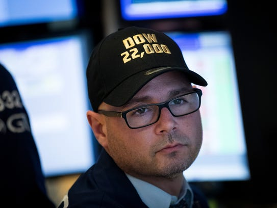 A trader wears a 'Dow 22,000' themed hat while working