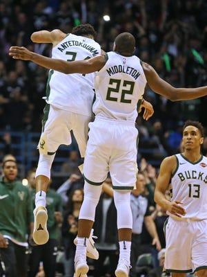 The Milwaukee Bucks' Giannis Antetokounmpo, left, and Khris Middleton, center, hope to do more celebrating this season as NBA basketball returns to Fiserv Forum.