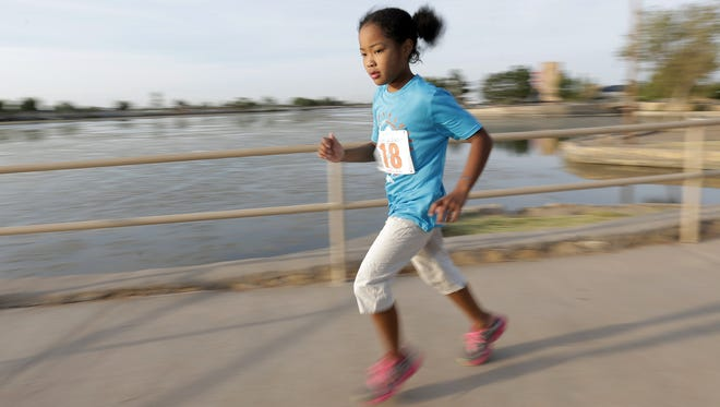 Elizabeth Glasper runs across a bridge at Ascarate Park as she nears the finish line at the Sun City Kids Splash and Dash.