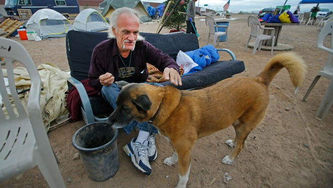 """""""12-string"""" & dog Penny live at Camp Alpha near the 202 and McKellips Drive Wednesday, Dec. 21, 2016 in Mesa, Ariz. Camp Alpha is a homeless encampment that focuses on housing veterans, but won't turn anyone away."""