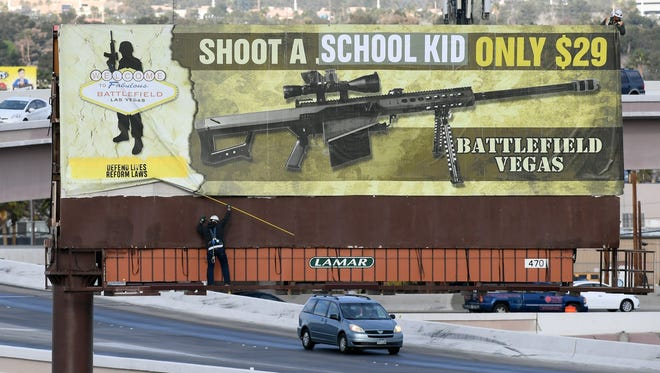 Workers are pictured removing a billboard poster for the Battlefield Vegas shooting range after it was vandalized.