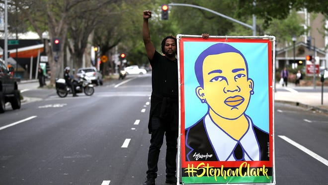 A Black Lives Matter protester holds an illustration of Stephon Clark during a march and demonstration through the streets of Sacramento.