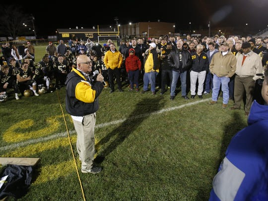 Retiring head coach Butch Simpson addresses dozens of current and past players during ceremonies honoring his 39 years leading the Yellowjackets following one last win, 29-8, against A.I. du Pont at Newark High School Friday.