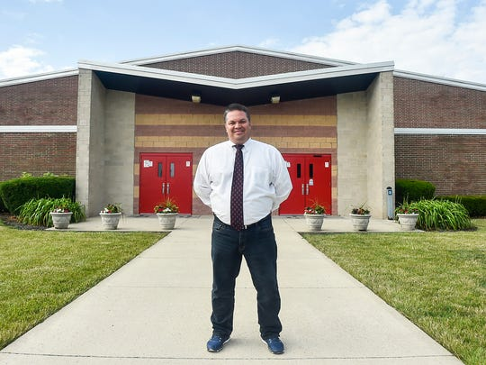 Principal Eric Holman stands in front of Pleasant High School. District officials hope to start building portions of the new K-12 facility next year.
