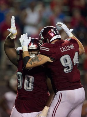 Troy defensive tackle Trevon Sanders (90) celebrates with Troy defensive end Seth Calloway (94) after a sack during the Troy vs South University NCAA football game on Wednesday, Oct. 11, 2017, in Troy, Ala. South Alabama defeated Troy 19-8.