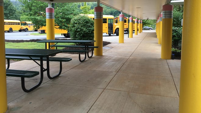 Art teacher Ernest Wince painted the green columns outside Avery's Creek Elementary School to look like giant pencils.
