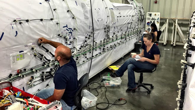 Workers at the B/E Aerospace plant in Great Falls stretch wire harnesses on top of an aircraft mockup.
