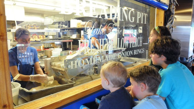 A group of kids gather around the breading pit at Jolly Roger Seafood House in Port Clinton to watch fish being breaded on Monday, Aug 4, 2014.