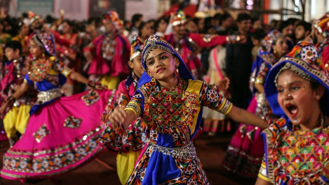 Indians wearing traditional attire participate in a Garba dance performance during the Navaratri festival celebrations in Mumbai, India, on Sept. 25, 2017.