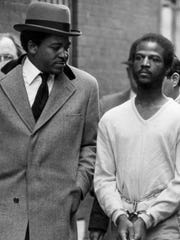 Percy Wilson walks with shackles on his wrists alongside defense attorney Leslie Isaiah Gaines in alley where the crime occurred. Percy Wilson was bound as he sat in court. Percy Wilson was accused in the May 1979 slaying of Cincinnati police officer Melvin Henze.