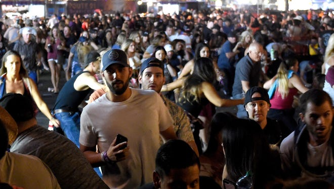 People flee the Route 91 Harvest country music festival grounds.
