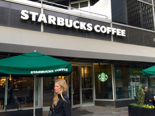 A woman walks past the Starbucks coffee shop on Denver's