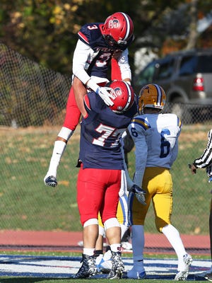 Stepinac's Jesse Brown (3) jumps into the arms of teammate Khaleb Celaj (77) after scoring a second quarter touchdown against Saint Peter's during the NYCHSFL semifinals at Archbishop Stepinac High School in White Plains Nov 15, 2015. Stepinac won the game 49-7.