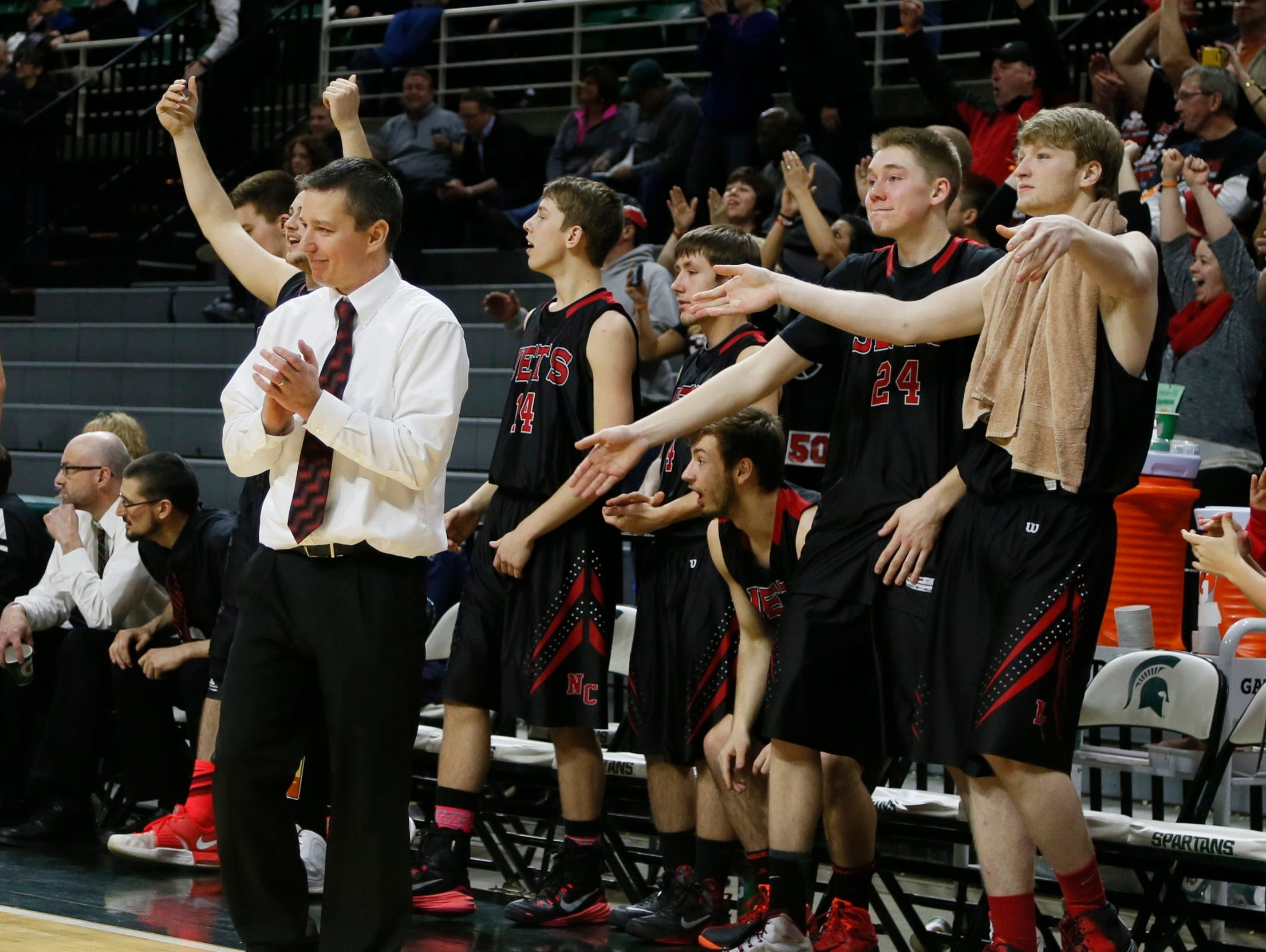 Powers North Central head coach Adam Mercier and players start to celibate as the last seconds dun out on their 71-46 win over Fulton-Middleton in MHSAA Boys Class D semi final basketball game on Thursday, March 26, 2015 in East Lansing.