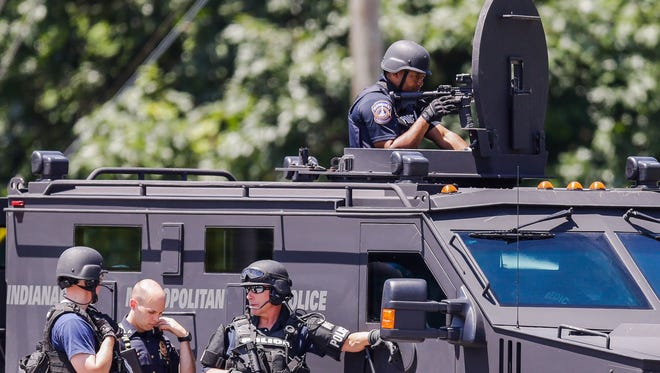 SWAT officers standby as police deal with a shooting suspect holed-up in a house near 46th Street and Evanston Avenue.