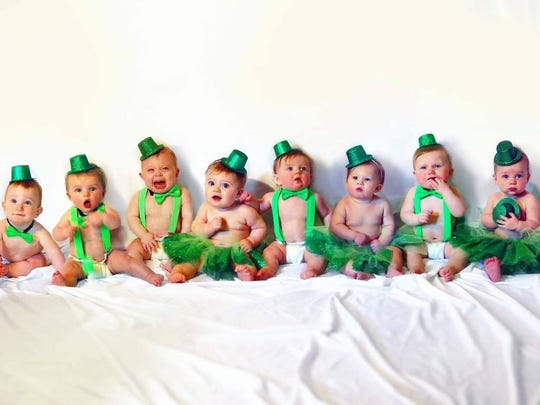 The eight babies born weeks apart pose for a St. Patrick's Day photo.