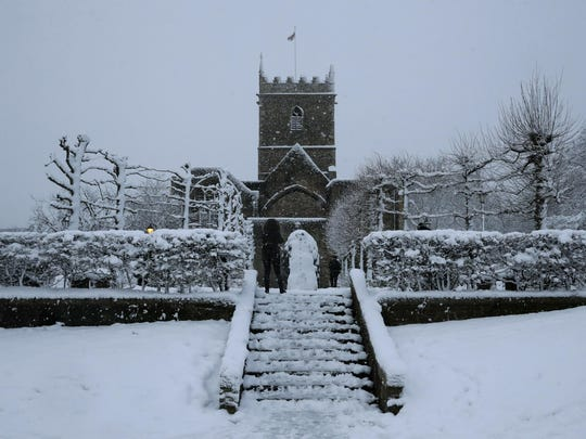 In this Feb. 1, 2019, photo, snow falls over St. Peter's Church in Bristol, south west England.