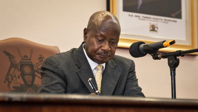 Uganda's President Yoweri Museveni signs a new anti-gay bill that sets harsh penalties for homosexual sex, in Entebbe on Monday.