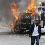 Patrick Semansky/APA man walks past a burning police vehicle Monday during unrest following the funeral of Freddie Gray in Baltimore. A man walks past a burning police vehicle, Monday, April 27, 2015, during unrest following the funeral of Freddie Gray in Baltimore. Gray died from spinal injuries about a week after he was arrested and transported in a Baltimore Police Department van. (AP Photo/Patrick Semansky)