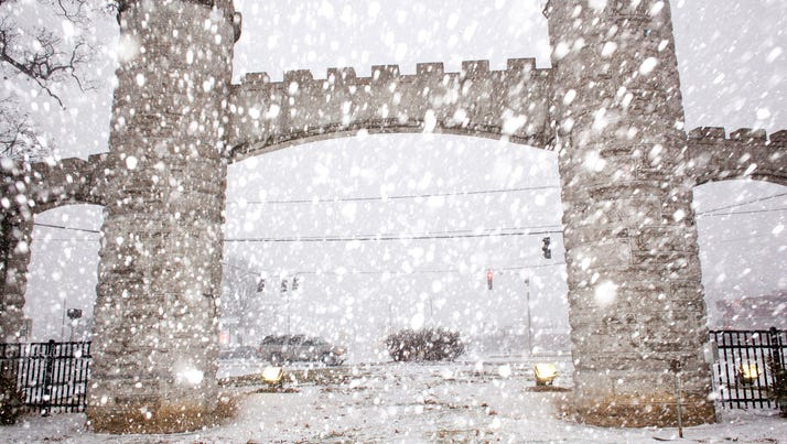 Snow falls near the entrance of Noble Park, Wednesday,