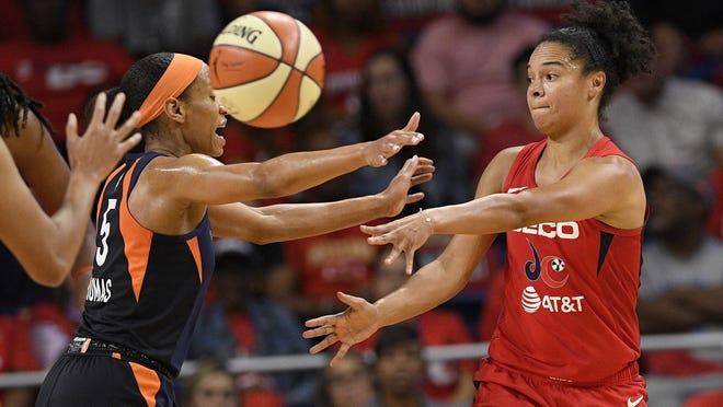 Washington Mystics guard Kristi Toliver, right, passes the ball against Connecticut Sun guard Jasmine Thomas (5) during Game 2 of last year's WNBA Finals.
