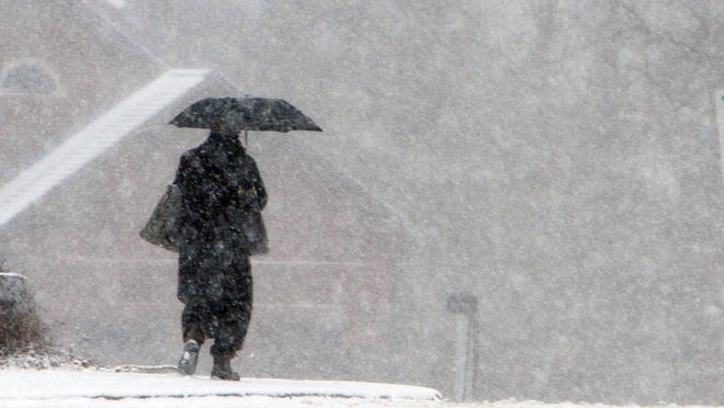 A commuter walks from the Katonah train station during a steady snowfall in January.
