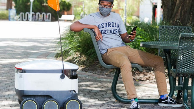 A GSU student uses an app to have food delivered by a robot on the Statesboro campus.