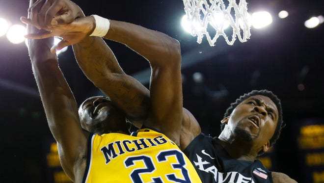 Michigan guard Caris LeVert (23) shoots and is fouled by Xavier forward Jalen Reynolds (1) in the first half at Crisler Center Friday.