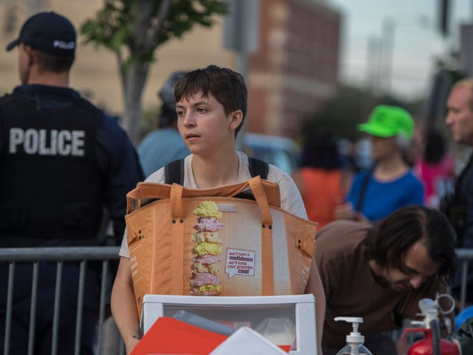 An Abolish ICE protester carries off supplies from