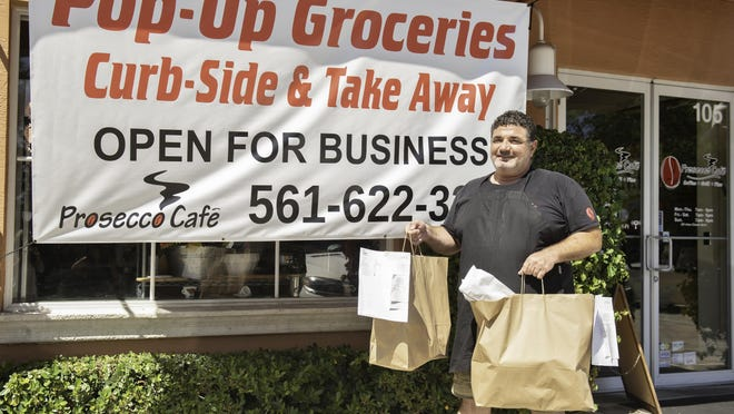 Avi Sekerel, owner of Prosecco Café, The Dancing Crane and Saquella Café, delivers a customer's take-out order Monday. Sekerel has converted his three restaurants into pop-up grocery stores.