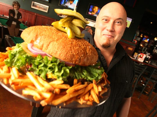 Mallie's owner Stephen Mallie with one of his bar's big burgers.