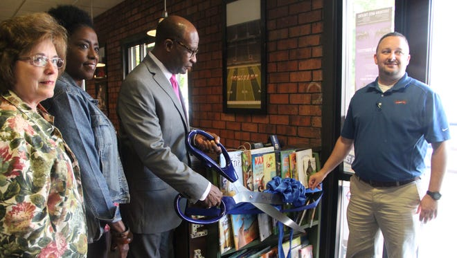 Hattiesburg Mayor Johnny DuPree, center, cuts the ribbon for the new library lounge at McAlister's Deli.