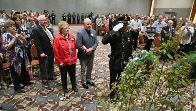 John James O'Brien (from left), grandson; Florence Ann O'Brien Timm, granddaughter; and David John O'Brien, great-grandson, lay a wreath in honor of Milwaukee Police Detective David J. O'Brien, who was killed by a bomb blast on Nov. 24, 1917, along with eight other Milwaukee police officers.  Milwaukee Police Officer Cliff Stephens (right) assists. The Greater Milwaukee Law Enforcement Memorial Service was held indoors at the Wisconsin Center.