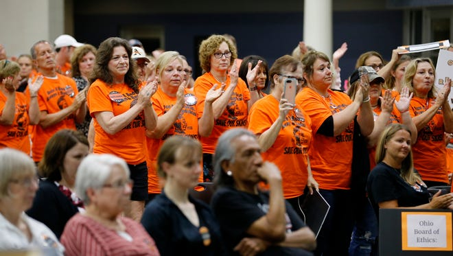 "Supporters in favor of keeping the name give a standing ovation after Andy Wolf makes a statement that ""people can find offense in anything"" during a meeting of the school board branding committee at Nagel Middle School in Anderson Township, Ohio, on Tuesday, June 12, 2018. The branding committee held a public meeting to discuss ending the use of the name ""Redskins""."