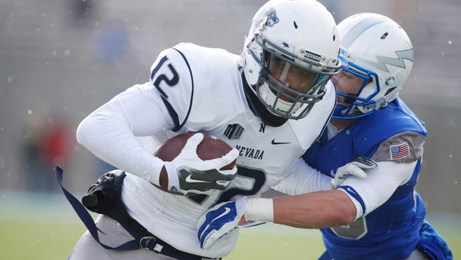 Nevada Wolf Pack wide receiver Hasaan Henderson is tackled by Air Force Falcons defensive back Gavin McHenry (20) during the first half at Falcon Stadium.