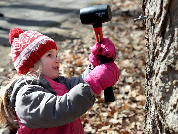 Natalie Carpus, 4, of Royal Oak, hammers a small device