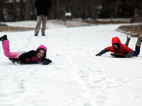 Mattie Montoleone, left, and her brother Bennett took advantage of the winter weather while sliding down Clement Drive in East Asheville Monday evening.