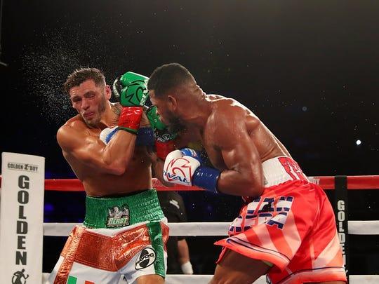 Sullivan Barrera throws a punch to Joe Smith Jr. during the WBC Intercontinental light heavyweight title fight.