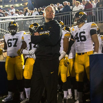 Iowa coach Kirk Ferentz leads his players out of the