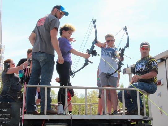 Students shoot arrows at a carp target in a pool at