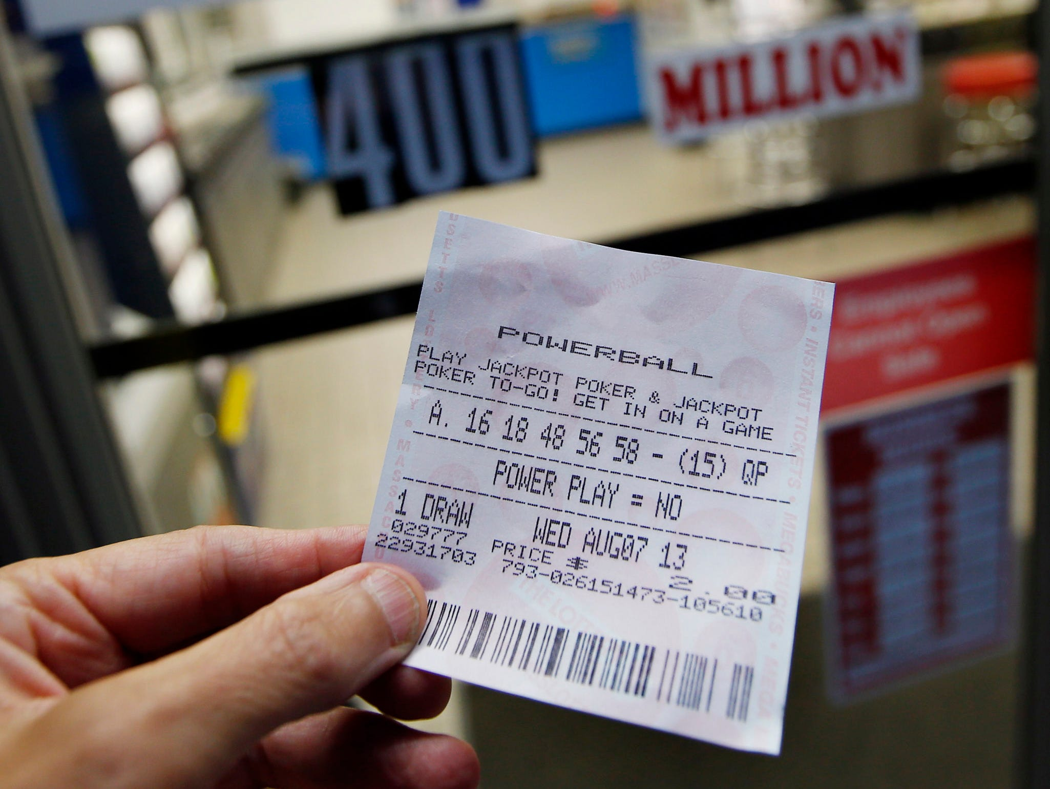 A person holds a Powerball ticket outside Ted's Mobil Mart in Methuen, Mass.
