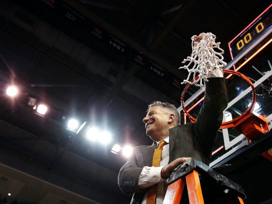 Auburn coach Bruce Pearl cuts down the net as Auburn celebrates its 79-70 win against South Carolina to capture an SEC regular-season title on March 3, 2018.