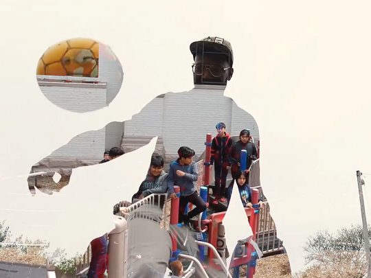 "In a still from the music video for ""El Color de la Libertad,"" Mikal Floyd-Pruitt plays soccer and students are hanging out at the playground."