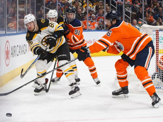 Boston Bruins' Kevan Miller (86) passes the puck as Edmonton Oilers' Adam Larsson (6) defends during the first period of an NHL hockey game Tuesday, Feb. 20, 2018, in Edmonton, Alberta. (Jason Franson/The Canadian Press via AP)