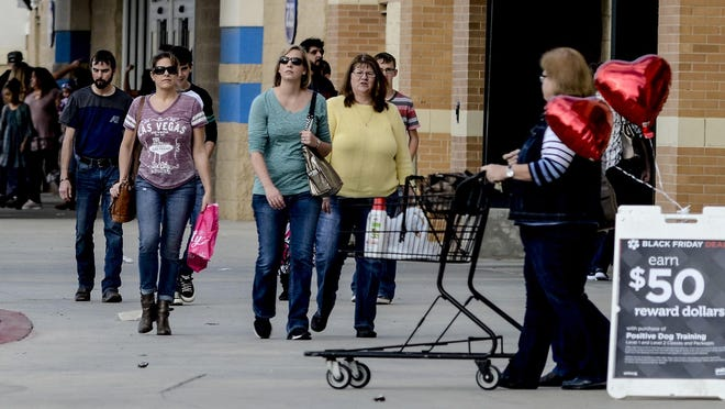 Shoppers make their way between stores at Schulman Crossing while looking for deals during a past Black Friday.