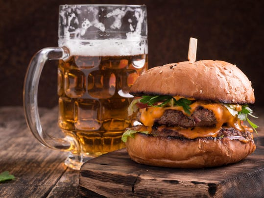 Fresh hamburger with a beer on a wooden table.