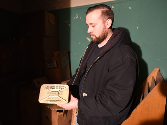 Gary Salvatoriello, supervisor of building and grounds at the Passaic Public Library, holds a box of survival biscuits inside the fallout shelter at the Reid Memorial Branch on Friday, Jan. 19, 2018.
