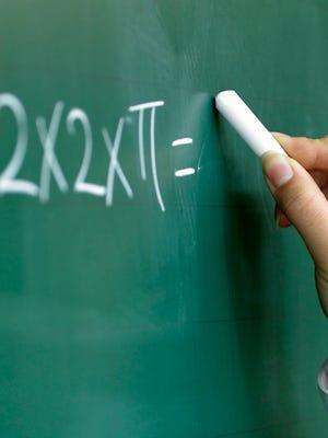Teacher shows mathematival equation.