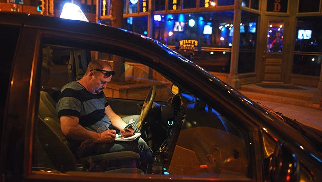 """John Hodgson, of Metro Cab, logs his fare after dropping clients off at Wiley's Tavern Friday, May 12, 2017, in Sioux Falls. """"You don't know what's coming next,"""" Hodgson said about driving a cab. """"That's the fun part,"""" he said. Hodgson is active on Snapchat, and communicates with about 50 percent of his clients on Friday and Saturday nights using the application, he said. Hodgson also has a liquor license and serves his clients alcohol."""